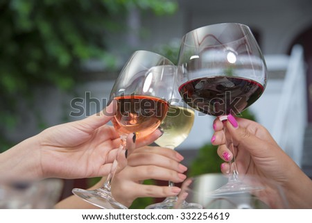 People holding wineglasses and toasting with wine. - stock photo