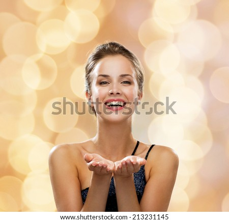 people, holidays, advertisement and luxury concept - laughing woman in evening dress holding something imaginary over beige lights background - stock photo