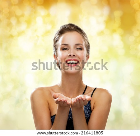 people, holidays, advertisement and luxury concept - laughing woman in evening dress holding something imaginary over yellow lights background - stock photo