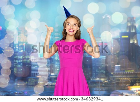 people, holidays and celebration concept - happy young woman or teen girl in pink dress and party cap over night city and holidays lights background - stock photo