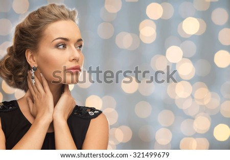 people, holidays and glamour concept - beautiful woman wearing earrings over lights background - stock photo