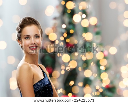 people, holidays and glamour concept - smiling woman in evening dress over christmas tree lights background - stock photo