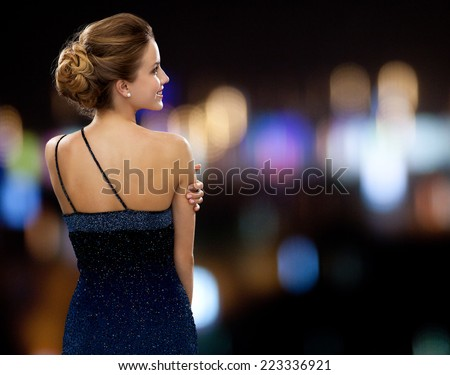 people, holidays and glamour concept - smiling woman in evening dress over night lights background - stock photo