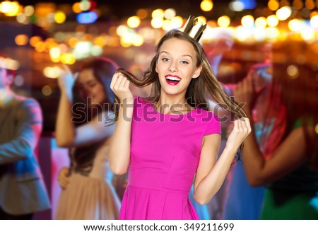 people, holidays, celebration and glamour concept - happy young woman or teen girl in pink dress and princess crown at night club party over crowd and lights background - stock photo