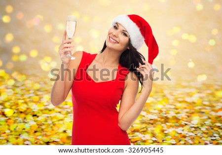 people, holidays, christmas and celebration concept - beautiful sexy woman in santa hat and red dress with champagne glass over golden glitter or lights background - stock photo