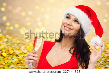 people, holidays, christmas and celebration concept - beautiful sexy woman in santa hat and red dress with champagne glass over yellow lights or golden confetti background - stock photo