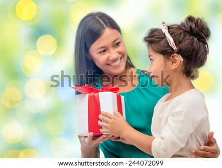 people, holidays, christmas and family concept - happy mother and daughter giving and receiving gift box over holiday green lights background - stock photo