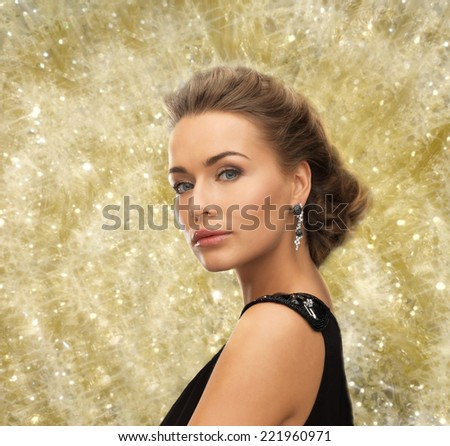 people, holidays, christmas and glamour concept - beautiful woman in evening dress wearing earrings over yellow lights background - stock photo