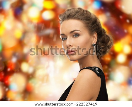 people, holidays, christmas and glamour concept - beautiful woman in evening dress wearing earrings over red lights background - stock photo