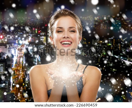 people, holidays, christmas and magic concept - laughing woman in evening dress holding something over snowy night city background