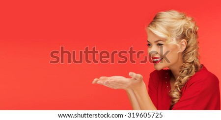 people, holidays, christmas, valentines day and advertisement concept - lovely woman in red clothes holding something on palms of her hands over red background - stock photo