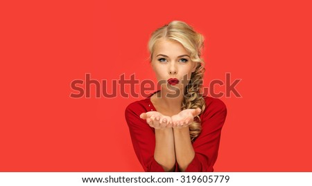 people, holidays, christmas, valentines day and advertisement concept - lovely woman in red dress blowing something on palms of her hands over red background - stock photo
