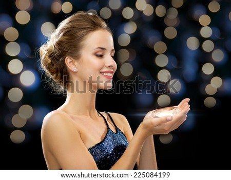 people, holidays, jewelry and glamour concept - smiling woman in evening dress holding big diamond over night lights background