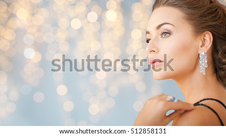 people, holidays, jewelry and luxury concept - close up of woman in evening dress with diamond earring over lights background