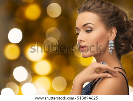 people, holidays, jewelry and luxury concept - woman in evening dress and diamond earring over lights background