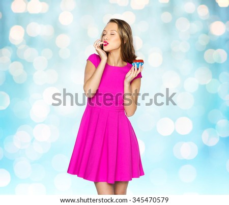 people, holidays, party, junk food and celebration concept - happy young woman in pink dress eating birthday cupcake over blue holidays lights background - stock photo