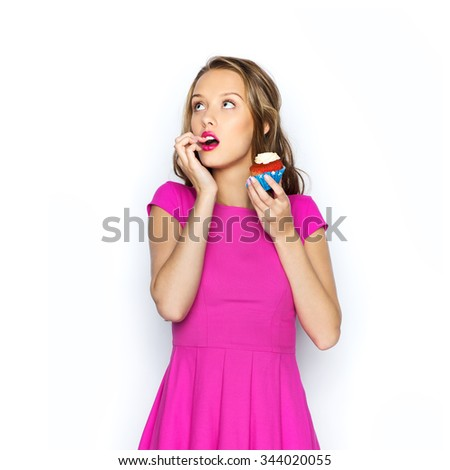 people, holidays, party, junk food and celebration concept - happy young woman or teen girl in pink dress with birthday cupcake - stock photo
