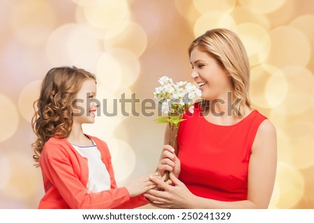 people, holidays, relations and family concept - happy little daughter giving flowers to her mother over beige lights background - stock photo