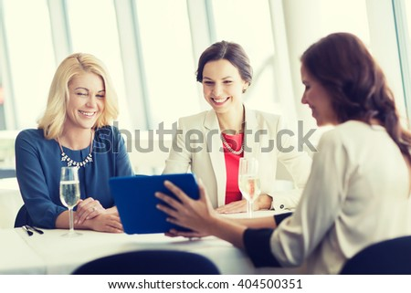 people, holidays, technology and lifestyle concept - happy women with tablet pc computer drinking champagne at restaurant