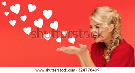 people, holidays, valentines day and love concept - lovely woman in red clothes sending heart shapes from on palms of her hands over red background - stock photo