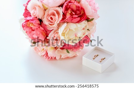 people, homosexuality, same-sex marriage and love concept - close up of gay female wedding rings in little box and flower bunch on table - stock photo