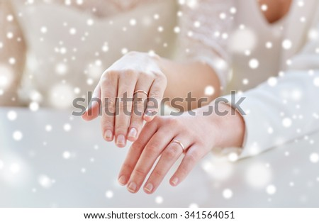 people, homosexuality, same-sex marriage and love concept - close up of happy lesbian couple hands showing wedding rings on over snow effect - stock photo