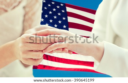 people, homosexuality, same-sex marriage and love concept - close up of happy lesbian couple hands putting on wedding ring over american flag background