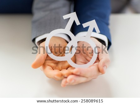 people, homosexuality, same-sex marriage and love concept - close up of happy male gay couple holding paper cutout love symbol - stock photo