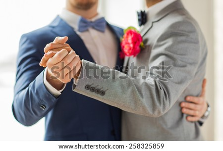 people, homosexuality, same-sex marriage and love concept - close up of happy male gay couple holding hands and dancing on wedding - stock photo
