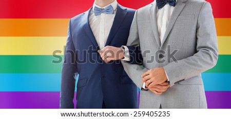 people, homosexuality, same-sex marriage and love concept - close up of happy male gay couple holding hands on wedding over rainbow flag background - stock photo