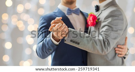 people, homosexuality, same-sex marriage and love concept - close up of happy male gay couple holding hands and dancing on wedding over holidays lights background - stock photo