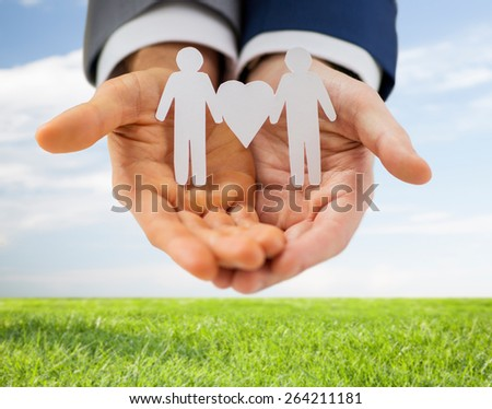 people, homosexuality, same-sex marriage and love concept - close up of happy male gay couple holding paper cutout love symbol over blue sky and grass background - stock photo