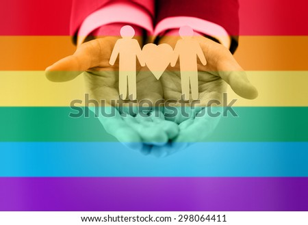 people, homosexuality, same-sex marriage and love concept - close up of happy male gay couple holding paper cutout love symbol over rainbow flag stripes background - stock photo