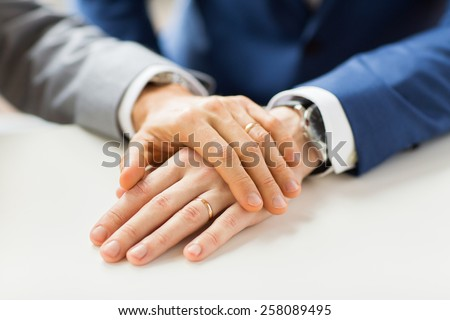 people, homosexuality, same-sex marriage and love concept - close up of happy male gay couple hands with wedding rings on - stock photo