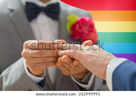 people, homosexuality, same-sex marriage and love concept - close up of happy male gay couple hands putting wedding ring on over rainbow flag background - stock photo