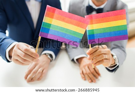 people, homosexuality, same-sex marriage and love concept - close up of happy male gay couple in suits and bow-ties with wedding rings holding rainbow flags - stock photo