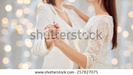people, homosexuality, same-sex marriage and love concept - close up of happy married lesbian couple dancing over holiday lights background - stock photo