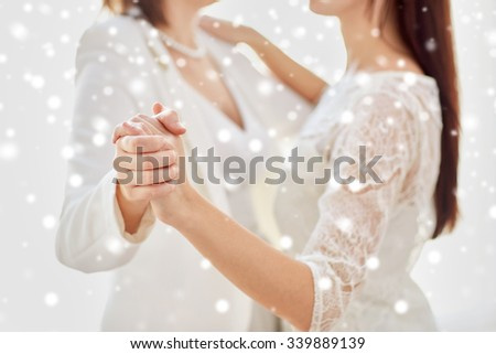 people, homosexuality, same-sex marriage and love concept - close up of happy married lesbian couple dancing over snow effect - stock photo