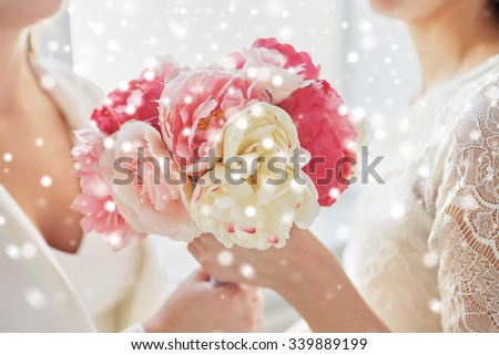 people, homosexuality, same-sex marriage and love concept - close up of happy married lesbian couple with flower bunch over snow effect - stock photo