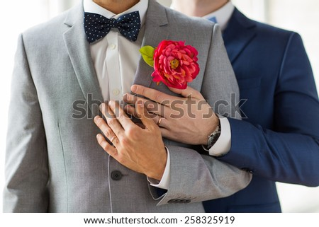 people, homosexuality, same-sex marriage and love concept - close up of happy married male gay couple in suits with buttonholes and bow-ties on wedding - stock photo