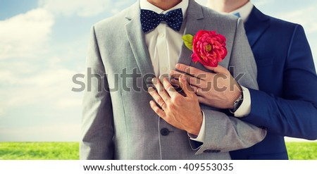 people, homosexuality, same-sex marriage and love concept - close up of happy married male gay couple in suits with buttonholes and bow-ties on wedding over blue sky and grass background - stock photo