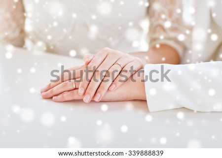 people, homosexuality, same-sex marriage and love concept - close up of lesbian couple hands with wedding rings over snow effect - stock photo