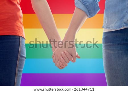 people, homosexuality, same-sex marriage, gay and love concept - close up of happy lesbian couple holding hands over rainbow flag background - stock photo