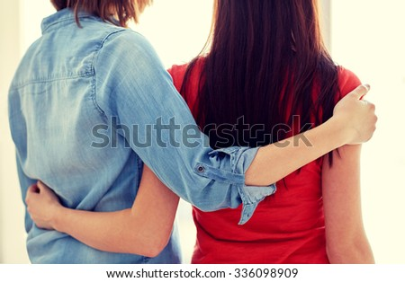people, homosexuality, same-sex marriage, gay and love concept - close up of happy lesbian couple hugging at home - stock photo