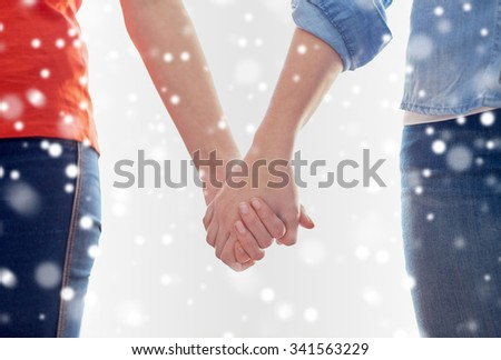 people, homosexuality, same-sex marriage, gay and love concept - close up of happy lesbian couple holding hands over snow effect - stock photo