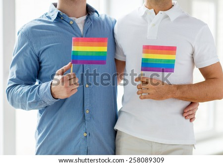 people, homosexuality, same-sex marriage, gay and love concept - close up of happy male gay couple hugging and holding rainbow flags at home - stock photo