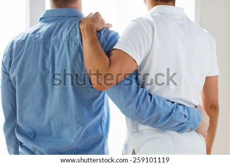 people, homosexuality, same-sex marriage, gay and love concept - close up of happy male gay couple or friends hugging from back - stock photo