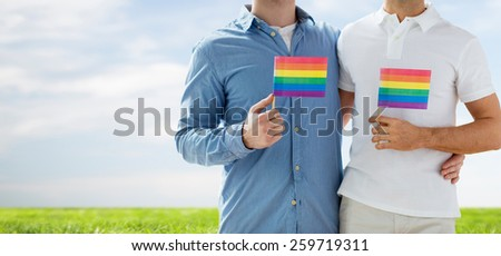 people, homosexuality, same-sex marriage, gay and love concept - close up of happy male gay couple hugging and holding rainbow flags over blue sky and grass background - stock photo