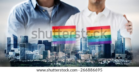 people, homosexuality, same-sex marriage, gay and love concept - close up of happy male gay couple hugging and holding rainbow flags over city background - stock photo