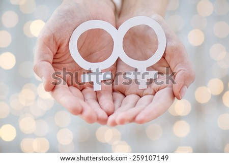 people, homosexuality, same-sex marriage, gay pride and love concept - close up of happy lesbian couple hands holding white paper venus symbol over holiday lights background - stock photo